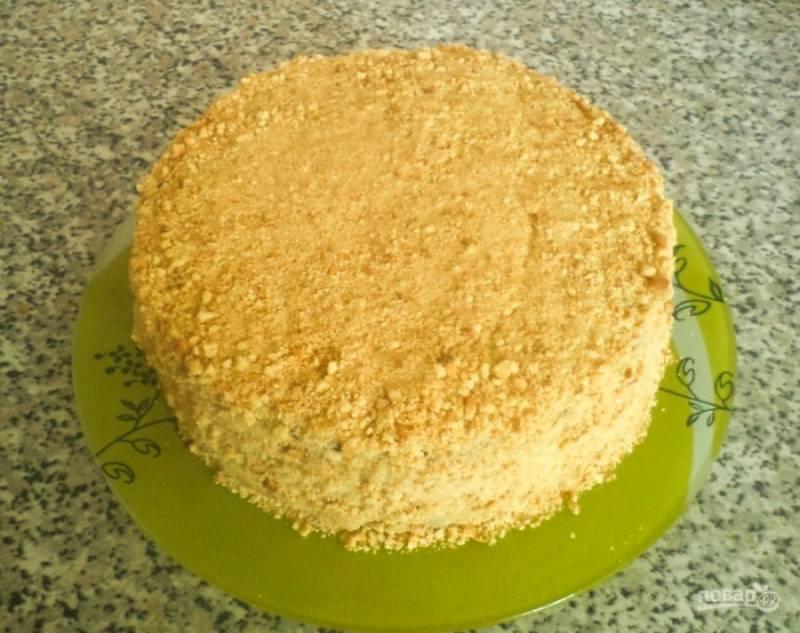 После того, как все коржи остынут, смажьте их кремом и соберите торт. Со всех сторон присыпьте торт измельченными крошками от остатков коржей. Поставьте торт в холодильник на пару часов, чтобы коржи пропитались кремом.