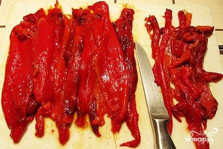 Охлажденный перец почистите от семя и плодоножек. Нарежьте пластами по 3 см и уложите в глубокую миску.