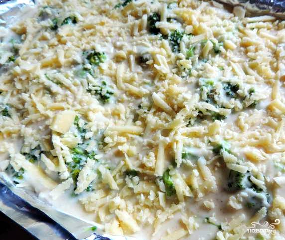 Брокколи выкладываем на противень, покрытый фольгой. Фольга не обязательна. Но так мне показалось надежней. Заливаем овощи получившимся сырным соусом. И поторопитесь, иначе соус застынет. Присыпаем сверху тертым сыром.