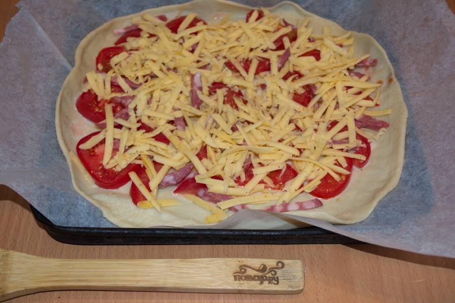 Смазываем пиццу томатным соусом. Выкладываем сверху помидоры, нарезанные кусочками, ветчину, колбасу или другое готовое мясо. Можно добавить овощи: лук, болгарский перец. Натрите на терке твердый сыр, посыпьте начинку тертым сыром.