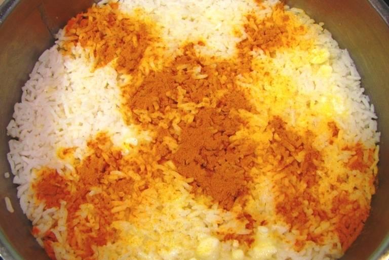 Поверх этого риса выкладываем оставшийся рис, поливаем его второй половиной сливочного масла и посыпаем куркумой. Тушим рис на медленном огне в течение часа, это можно сделать как на плите, так и в духовке (при 180 градусах на самом нижнем ярусе).