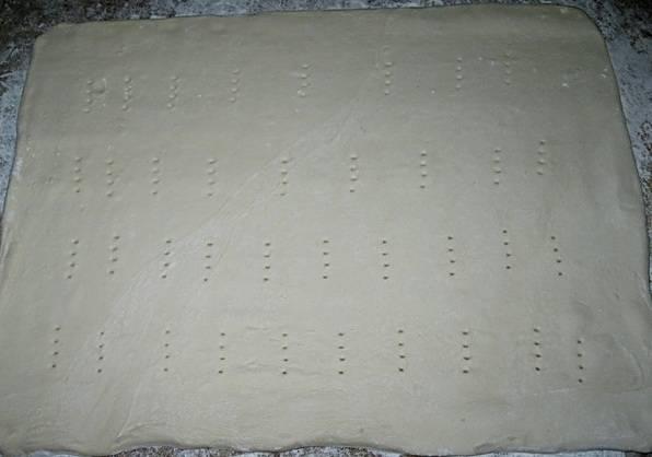 Когда тесто разморозится, его необходимо немного раскатать и проткнуть вилочкой по всей поверхности.