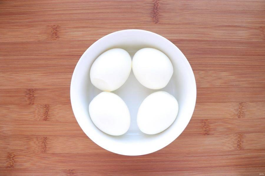 Куриные яйца сварите вкрутую и очистите. Два из них нарежьте кубиками, а другие два оставьте для украшения салата.