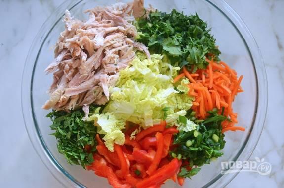 2. После этого мелко нашинкуйте морковь, перец, капусту, лук, мяту и кинзу. Всё соедините в салатнице вместе с курицей.