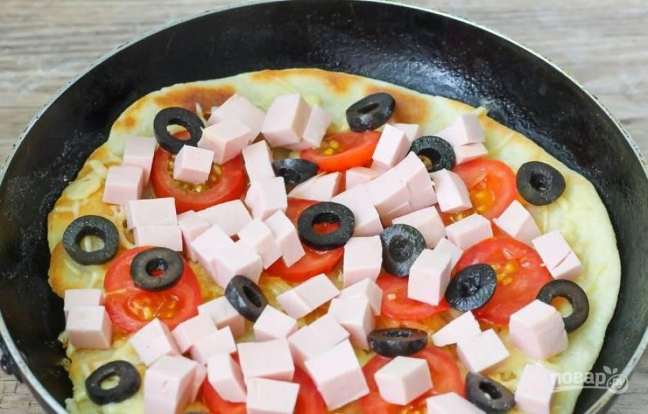 Колбасу нарежьте кубиками. Томаты вымойте и обсушите, нарежьте их тонкими кружочками. Откройте банку черных оливок и нарежьте их кружочками. Выложите все ингредиенты на пиццу.