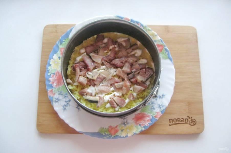 Филе сельди нарежьте небольшими кусочками и выложите на картофель. Покройте слоем майонеза.