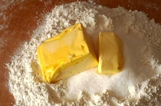 Сначала сделайте тесто. Просейте на доску 3 - 3,5 стакана муки. Сверху насыпьте 3/4 стакана сахара и добавьте 250 граммов размягченного маргарина.