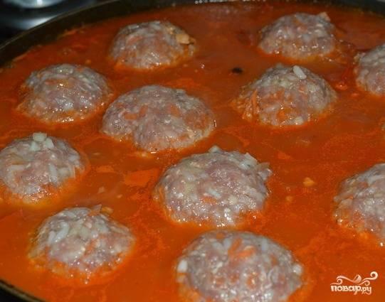 Скатываем шарики из фарша и риса, смачивая руки водой перед каждым комочком. Перекладываем томатную смесь в глубокую сковороду. Добавляем стакан воды. Тефтели помещаем в получившийся томатный сок, ставим все в духовку на 20 минут.