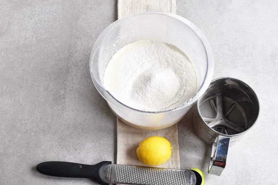 Смешайте муку с разрыхлителем и просейте поверх яиц. Добавьте немного тертой лимонной цедры.