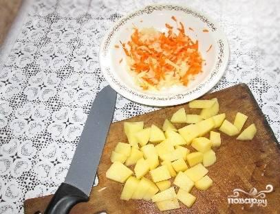 Нарезаем очищенную картошку на кубики, бросаем ее в бульон вариться. Очищаем луковицу от шелухи, нарезаем мелко. Морковь чистим, промываем водой и трем на терке. Овощи подготовлены.