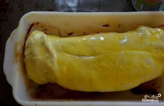 Достаньте слоеное тесто из морозилки, дайте ему растаять. В рецепте используется готовое тесто, но вы можете сделать его и самостоятельно. Раскатайте его, заверните в него подготовленную свинину. Смажьте сверху взбитым яйцом — и снова положите в форму.