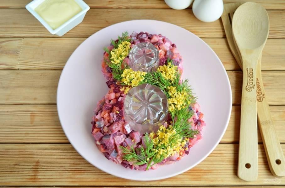 Для украшения салата отварите куриное яйцо, белок не понадобился. Положите веточки укропа на салат, желтками сделайте цветы мимозы.
