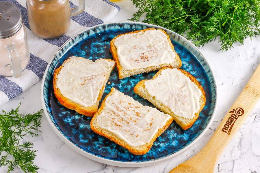 Смажьте каждый ломтик хлеба майонезом любой жирности, можно использовать постный майонез или чесночный.