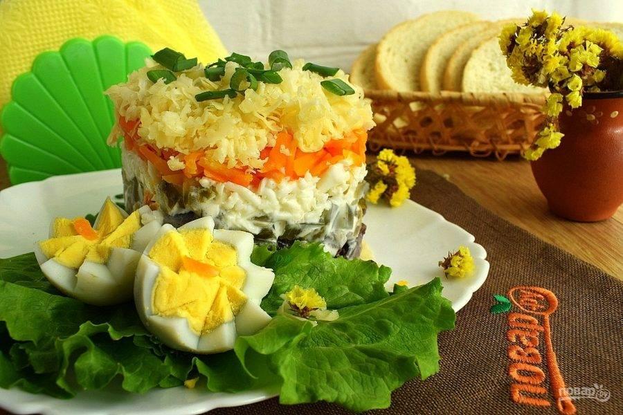 Выложите пару листьев салата на блюдо для подачи. Поставьте сервировочное кольцо, выложите салат слоями: куриная печень, лук, огурец, яйца, сыр. Промажьте каждый слой, кроме верхнего, соусом. Дайте салату немного настояться, аккуратно снимите сервировочное кольцо, подавайте блюдо к столу.