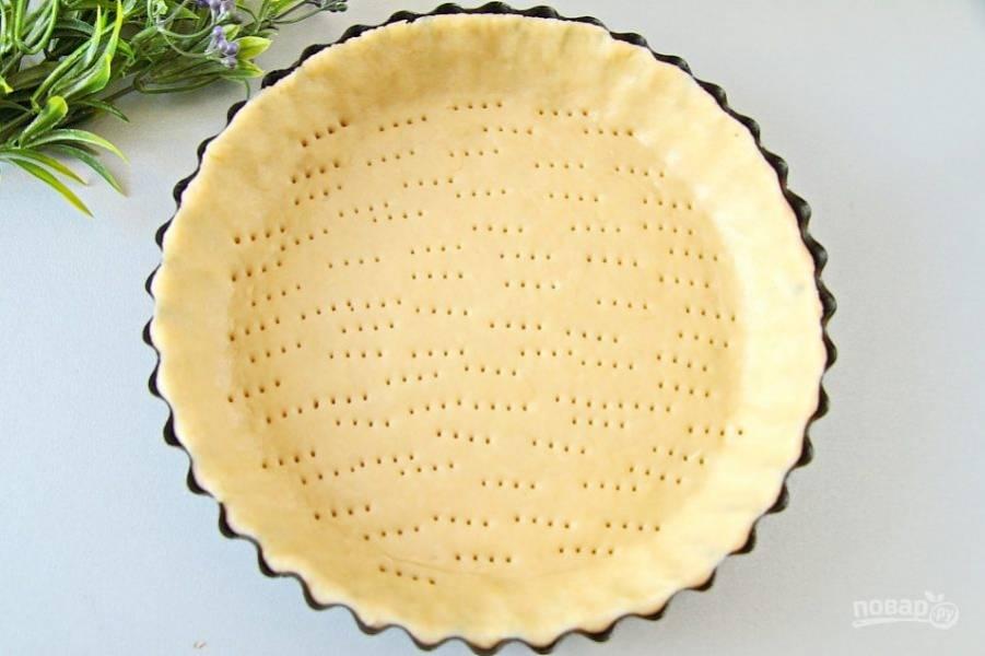 Достаньте тесто и раскатайте его по размеру формы, у меня – в диаметре 19 см. Аккуратно перенесите и сделайте руками бортики 2-3 см. высотой, проколите дно вилкой, как на фото.