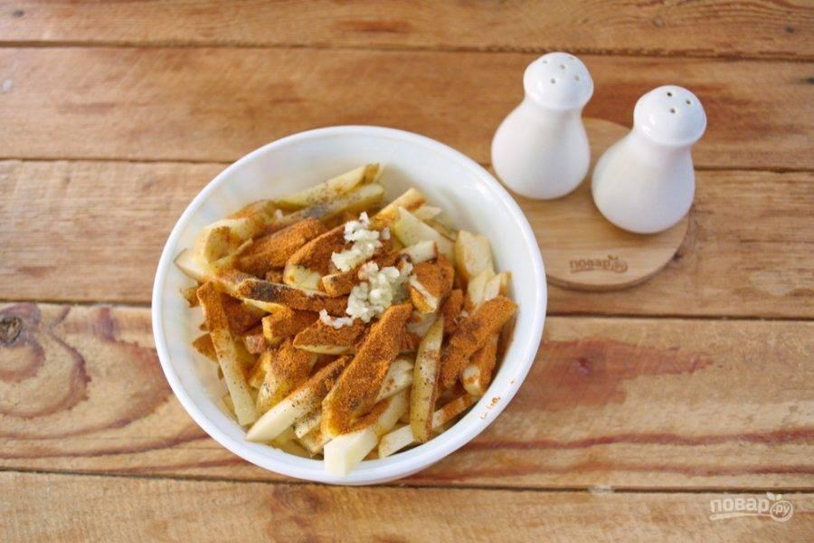 Поместите картофель в миску, добавьте специи (красный молотый перец, паприку, черный молотый перец, кориандр, соль, чеснок, выдавленный через пресс, или сушеный чеснок).