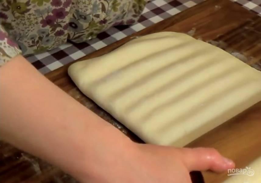 4. Подошедшее тесто раскатайте в прямоугольник и поместите на половину теста раскатанное сливочное масло. Прикройте его второй половиной теста и аккуратно раскатайте в пласт толщиной 1 см, периодически приподнимая скалку, не переворачивая тесто на обратную сторону.