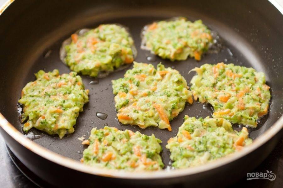 Перемешиваем овощи с зеленью, желтком яйца, солью, перцем, добавляем немного муки. Разогреваем сковороду, вливаем масло, выкладываем ложкой и распределяем блинчики. Жарим с одной стороны минуты полторы, затем переворачиваем. Если надо, переворачиваем снова.