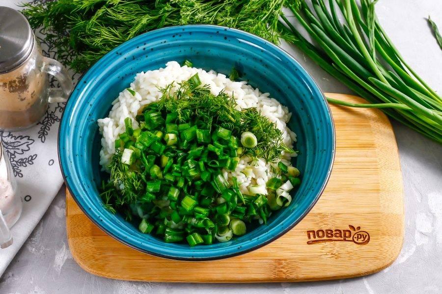 Выложите остывший рис в глубокую емкость. Промойте зеленый лук и укроп, измельчите зелень и добавьте в емкость к рису.