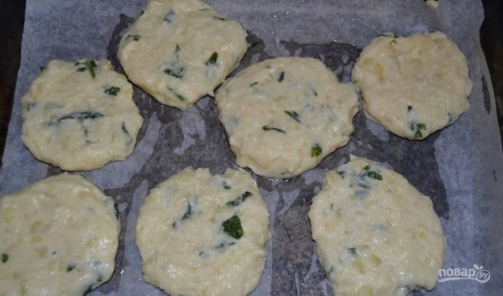 На противень расстелите пергаментную бумагу. На неё разложите лепёшки из картофельного теста.