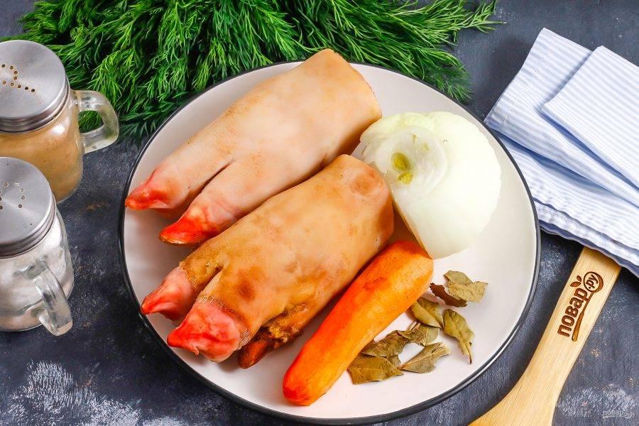 Подготовьте указанные ингредиенты. Свиные ножки ошпарьте кипятком и счистите с них загрязнения с помощью ножа, соскребите их. Если потребуется, то ошмалите над газовой конфоркой и снова промойте, соскребите. Очистите морковь и лук от кожуры, промойте.