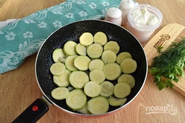 На оставшемся масле обжарьте порционно кружки кабачка с двух сторон до румяной корочки. Каждую порцию снимайте со сковороды, слегка смазывайте ее и обжаривайте следующую партию.