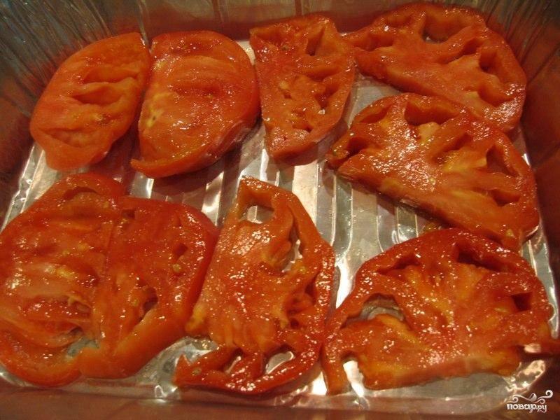 Берем форму для выпекания, слегка смазываем оливковым маслом. Выкладываем полукольцами нарезанный крупный помидор.