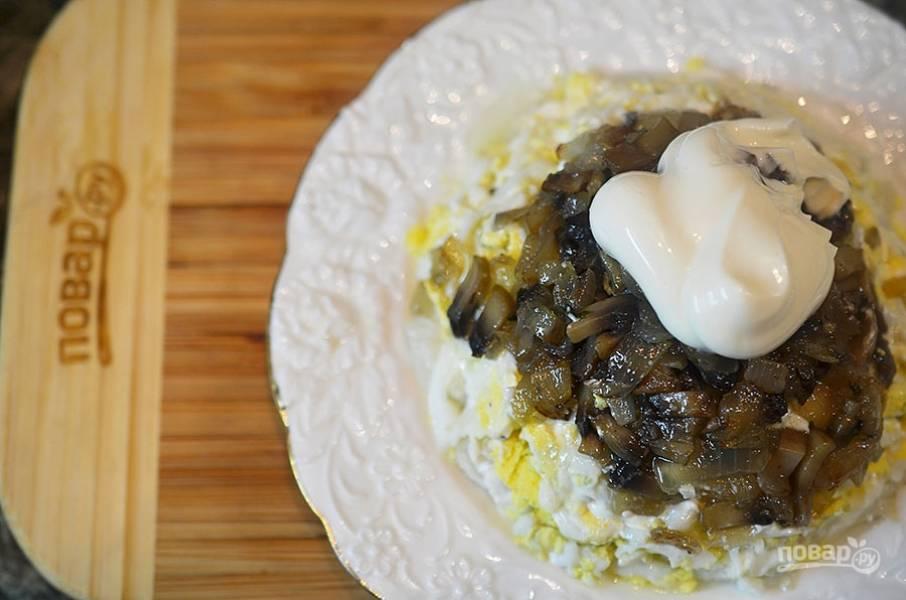 Затем горкой выложите жареные охлажденные грибы и смажьте обильно майонезом с хреном.