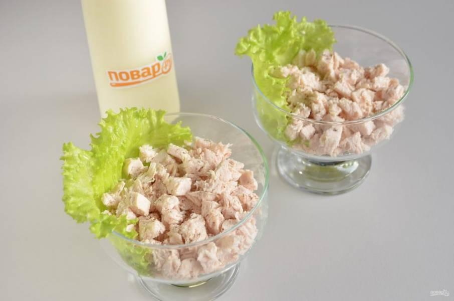 3. Все готово для сборки салата, можно использовать листья салата для украшения, а можно обойтись и без них. Первый слой — вареная курица, соль, перец и майонезная сетка.