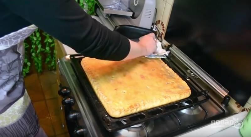 Духовку разогрейте до 180 градусов. Поставьте в нее пирог и запекайте сорок минут. Затем достаньте его из духовки и смажьте сливочном маслом. Накройте пирог полотенцем и дайте ему немного остыть.