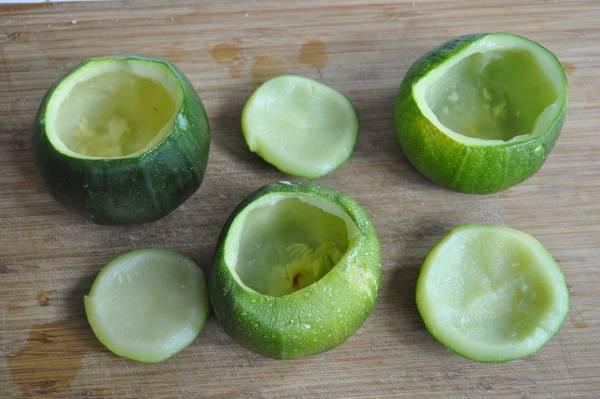 """1. Если у вас такие же кабачки, срезаем с них """"шапочку"""" и вырезаем мякоть. Натираем каждую корзинку солью и специями. Можно капнуть оливкового масла. Выкладываем в форму для запекания."""