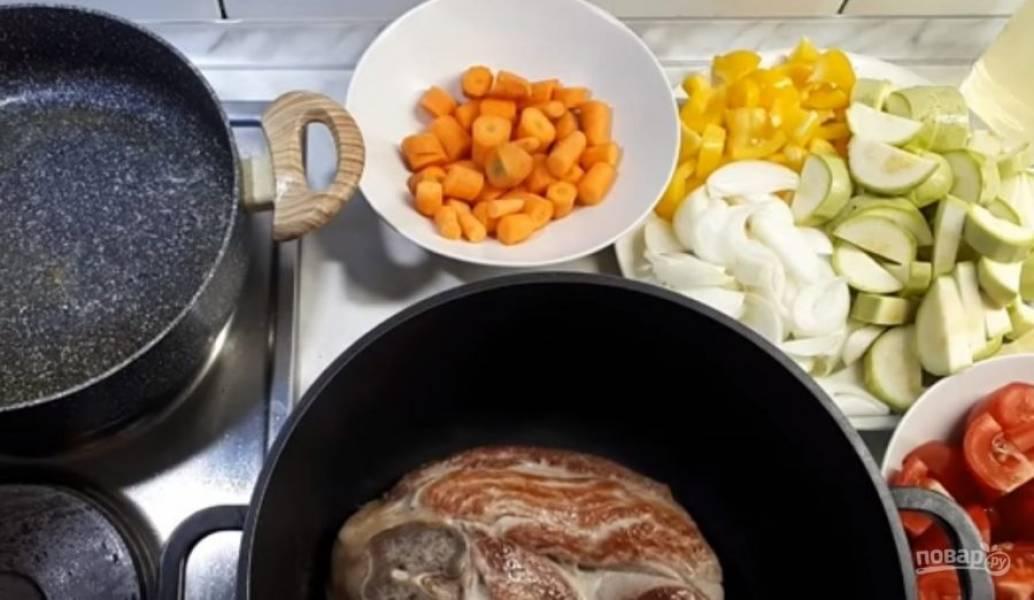 2.  Не снимая кожуру с помидоров, разрежьте их на 4 части. Зелень измельчите. На разогретую сковороду вылейте растительное масло и выложите мясо целым куском (не нарезая его на небольшие кусочки). Обжарьте мясо с двух сторон и переложите в кастрюлю.