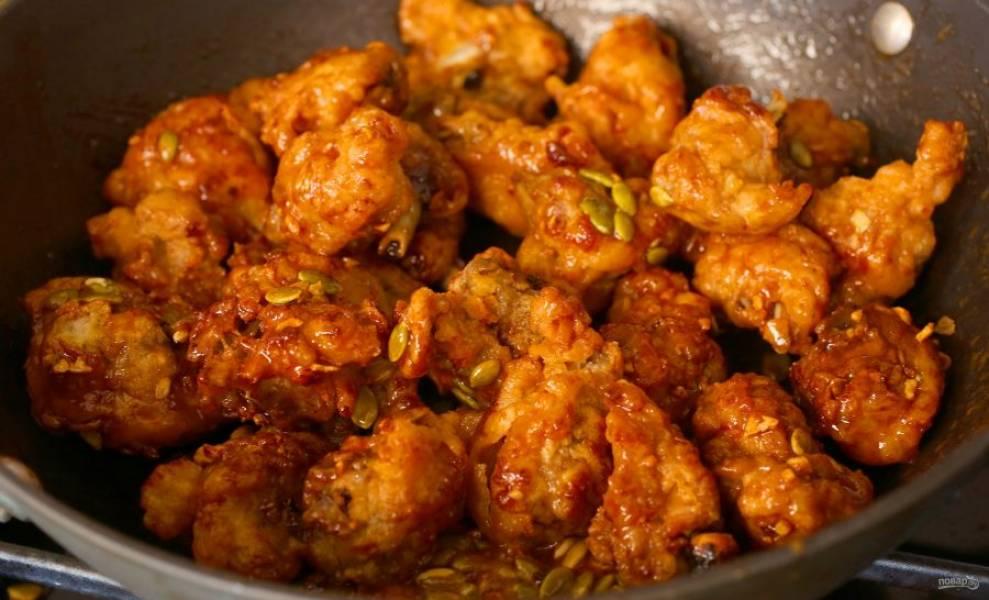 Отправьте в соус курицу и тыквенные семечки, протушите минутку и подавайте.