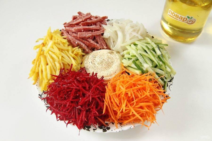 На большую тарелку выложите горками картофель, лук, колбасу, огурец, морковь и свеклу, чередуя цвета. В центр поместите майонез. Поперчите.