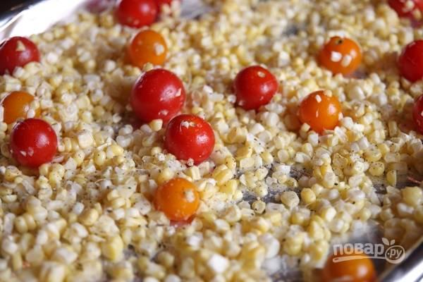 2. Подготовьте противень. Выложите на него кукурузу, вымытые и обсушенные помидоры, очищенные зубчики чеснока. Полейте небольшим количеством растительного масла и отправьте в разогретую до 190 градусов духовку.