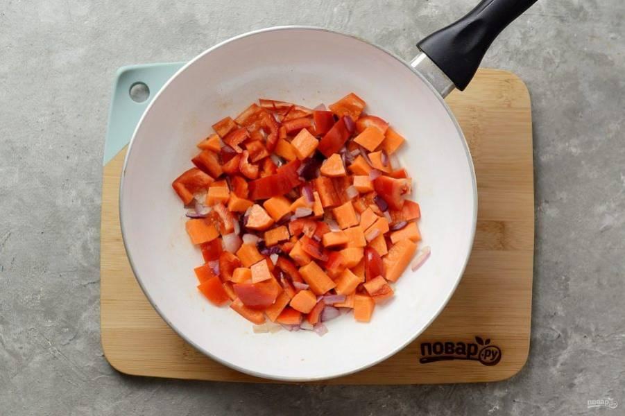 Нарежьте кубиками лук, чеснок, морковь и перец. Обжарьте в сковороде в начале лук и чеснок, а потом добавьте морковь и красный перец.