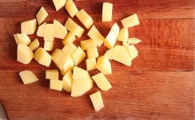 Режем кубиками картофель и добавляем в бульон.