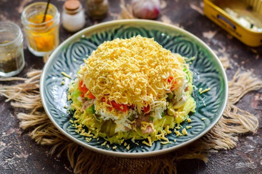 Завершающим слоем выложите натертые на мелкой терке желтки. Пропитайте салат час и подавайте к столу.
