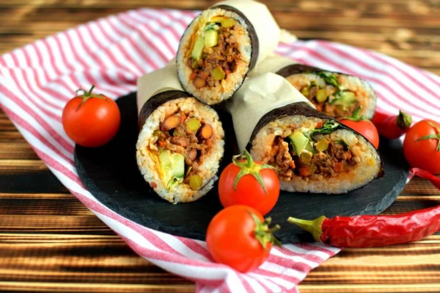 Готовые роллы разрежьте наискосок мокрым ножом, оберните каждую половинку бумагой или салфеткой и подавайте с соусами по вашему вкусу – вассаби или кетчуп.