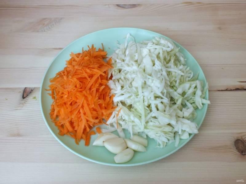 Нашинкуйте капусту, натрите на крупной терке морковь, очистите чеснок.