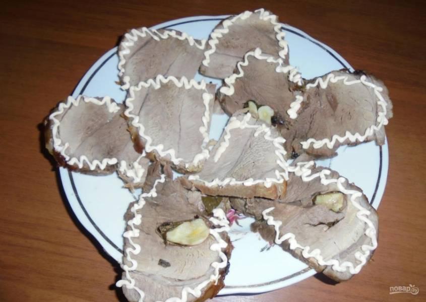 9.Остужаю мясо, затем снимаю нитки и нарезаю блюдо кусочками. Перед подачей на стол нарезаю его и украшаю майонезом.