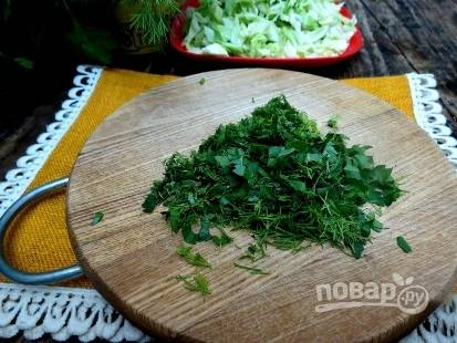 Дальше доводим борщ до кипения и добавляем квашеную капусту, соль, перец, яблочный уксус и мелко нарезанную зелень.