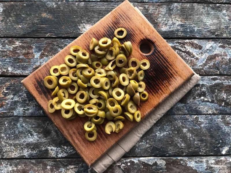 Оливки нарежьте кружочками и добавьте к остальным ингредиентам.