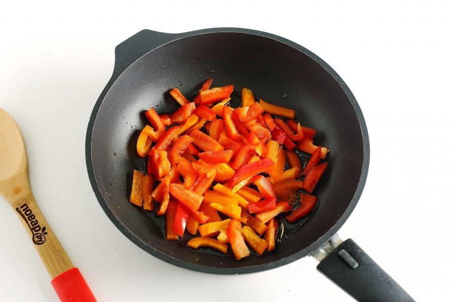 В сковороде разогрейте масло. Выложите нарезанный небольшой соломкой болгарский перец.