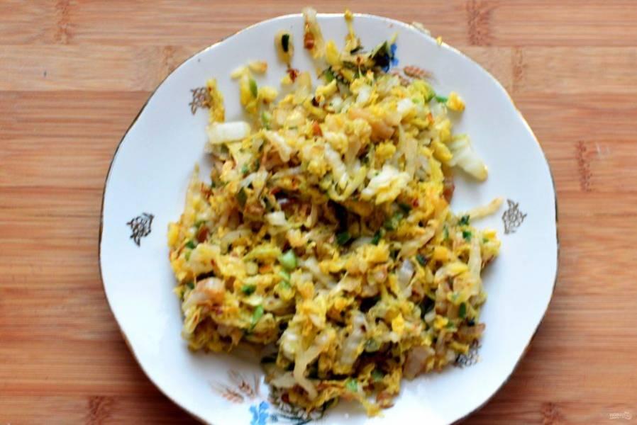 За это время приготовьте начинку. Перепелиные яйца отварите и остудите. Капусту и зеленый лук тонко нашинкуйте и обжарьте на минимуме масла до аппетитного запаха поджаренной капусты. Посолите и поперчите капусту по вкусу, добавьте крупно потолченный тмин, перемешайте и остудите начинку.