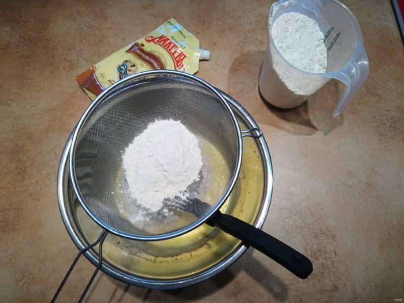 5. Вводите в тесто просеянную муку, постоянно перемешивайте. Прямо в миску с мукой просейте также пекарский порошок.