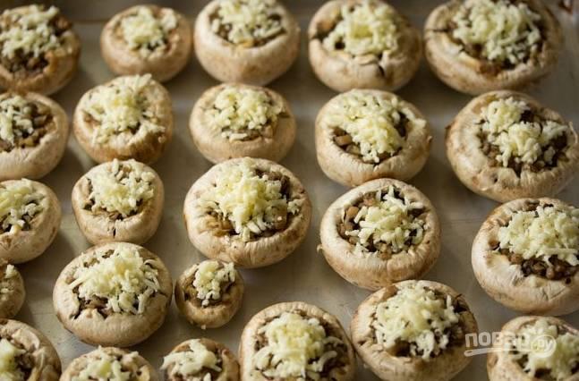Духовку разогрейте до 180 градусов, присыпьте грибы тертым сыром и отправьте запекаться на 20 минут.
