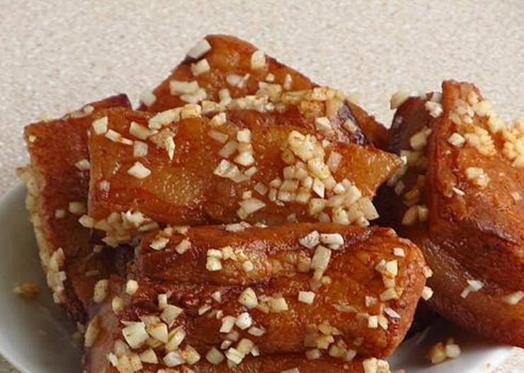 Натрите варенное сало красным перцем, а затем чесноком.