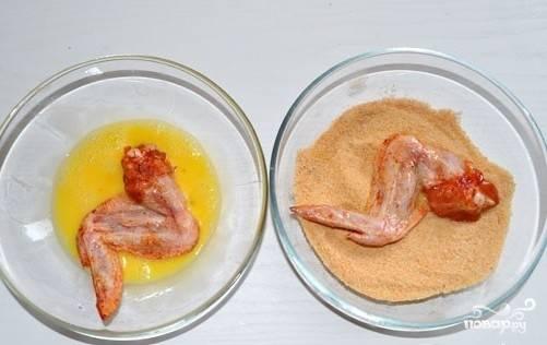 В одну миску насыпаем панировочные сухари, а в другой взбиваем яйцо с молоком. Окунаем каждое крылышко по очереди сначала в яичную смесь, а затем хорошенечко обваливаем в сухарях.