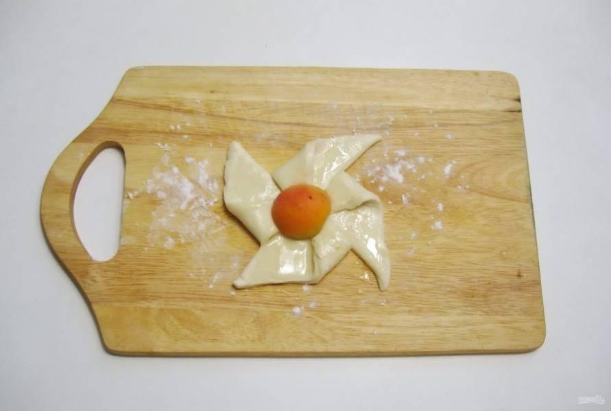 В центр слойки выложите половинку абрикоса.